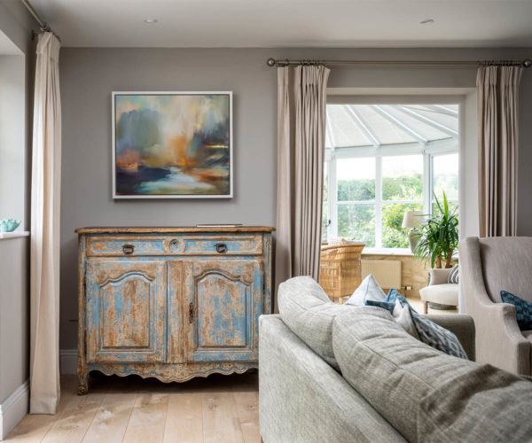 antique cabinet and modern painting in a country house. Corner sofa in blues and greys