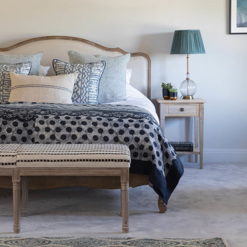 Blue bedroom decor with rug and bench at foot of bed