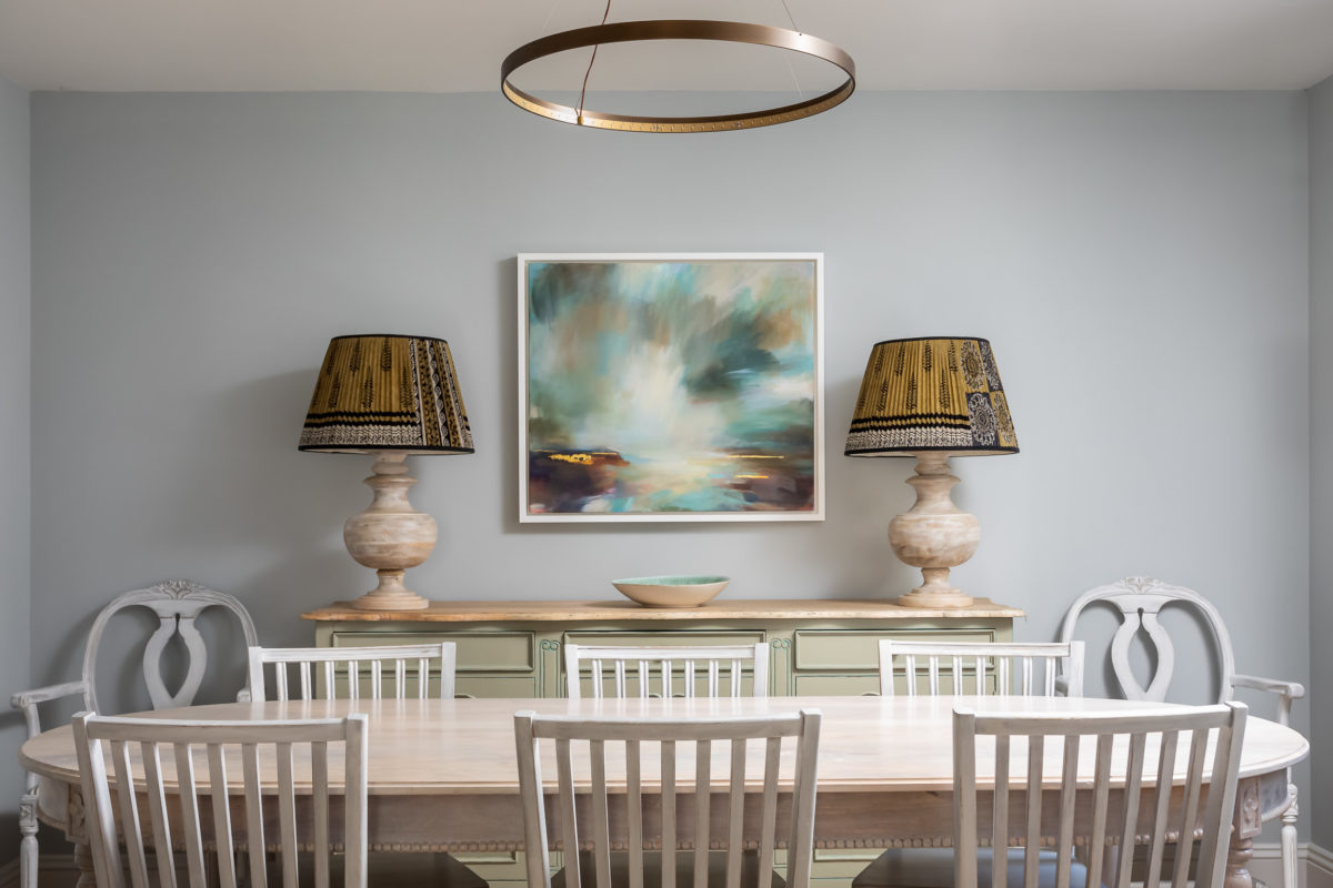 Swedish style dining room with table and chairs, modern painting and antique cabinet. Large table lamps