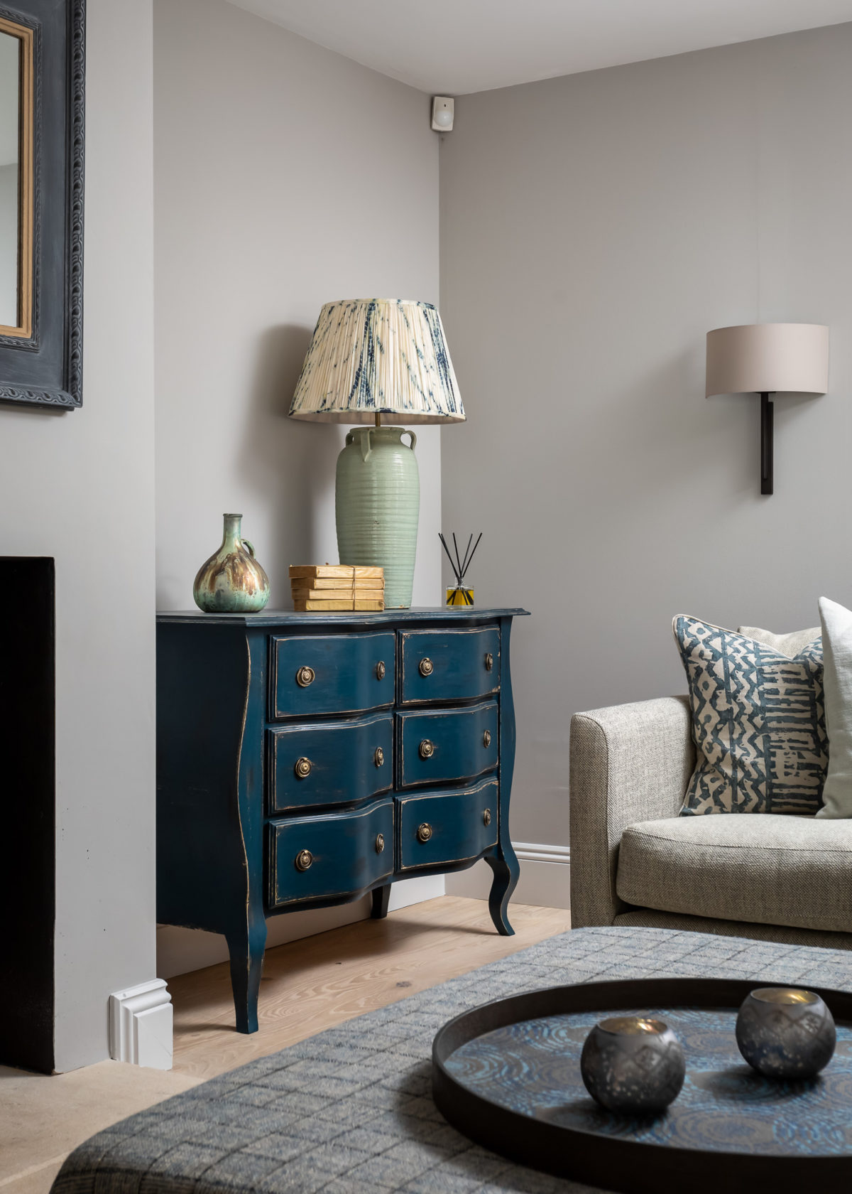 Antiqued blue painted chest in living room with corner sofa and footstool