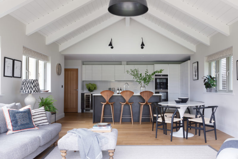 Modern kitchen in a barn conversions with sofa, footstool and chaise. Round dining table in white, black dining chairs