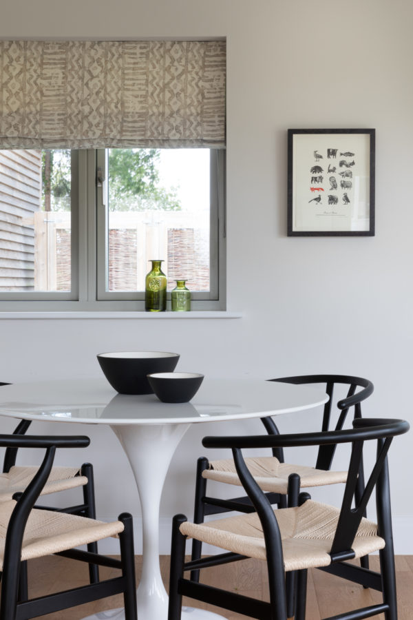 modern kitchen with round tulip table and black Hans Wegner chairs