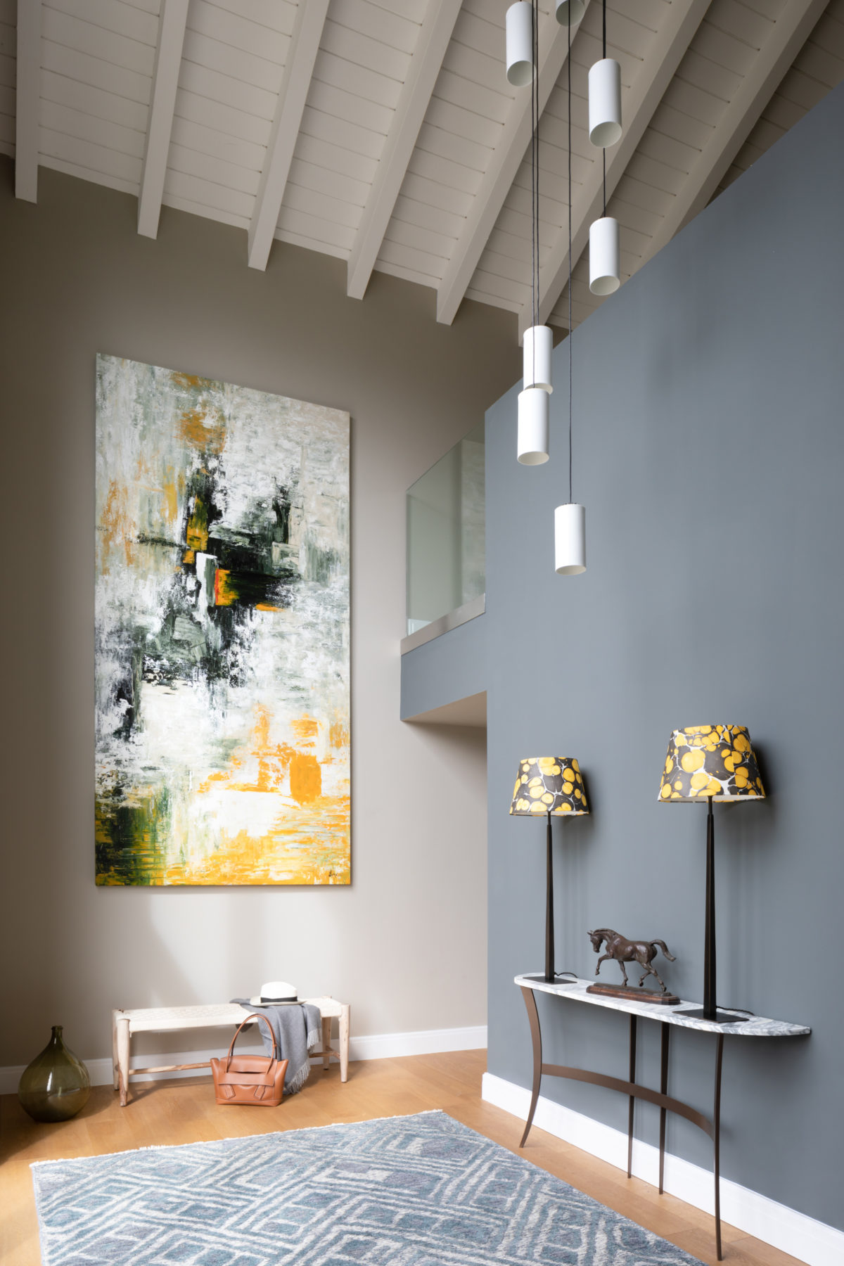 large artwork in galleried hall. Tall table lamps in console table under multi pendant light