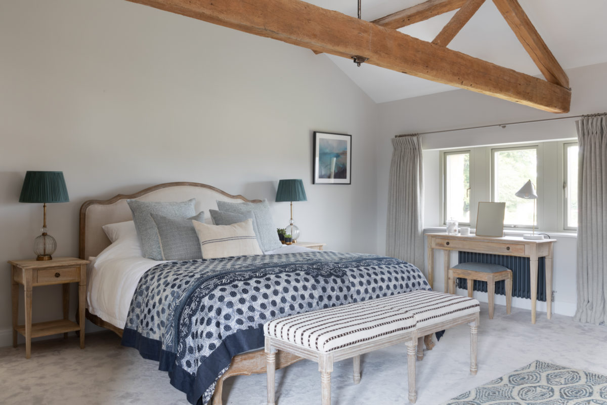 Blue and grey bedroom in Cotswold modern stone barn conversion