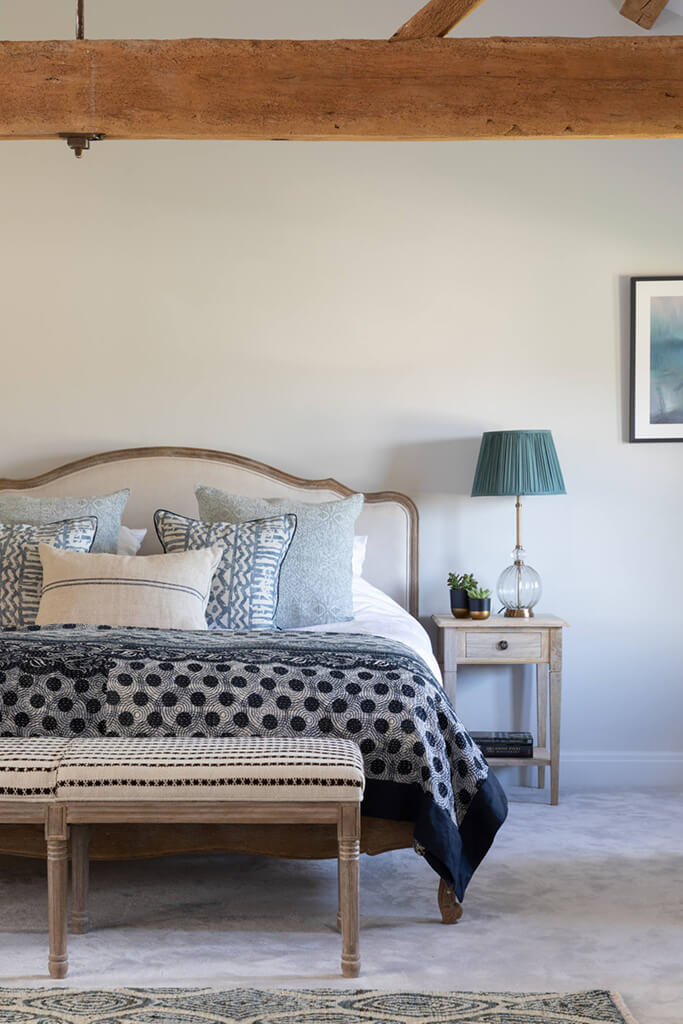 Master bedroom with wood beams, natural textures and colours and blues; grey walls