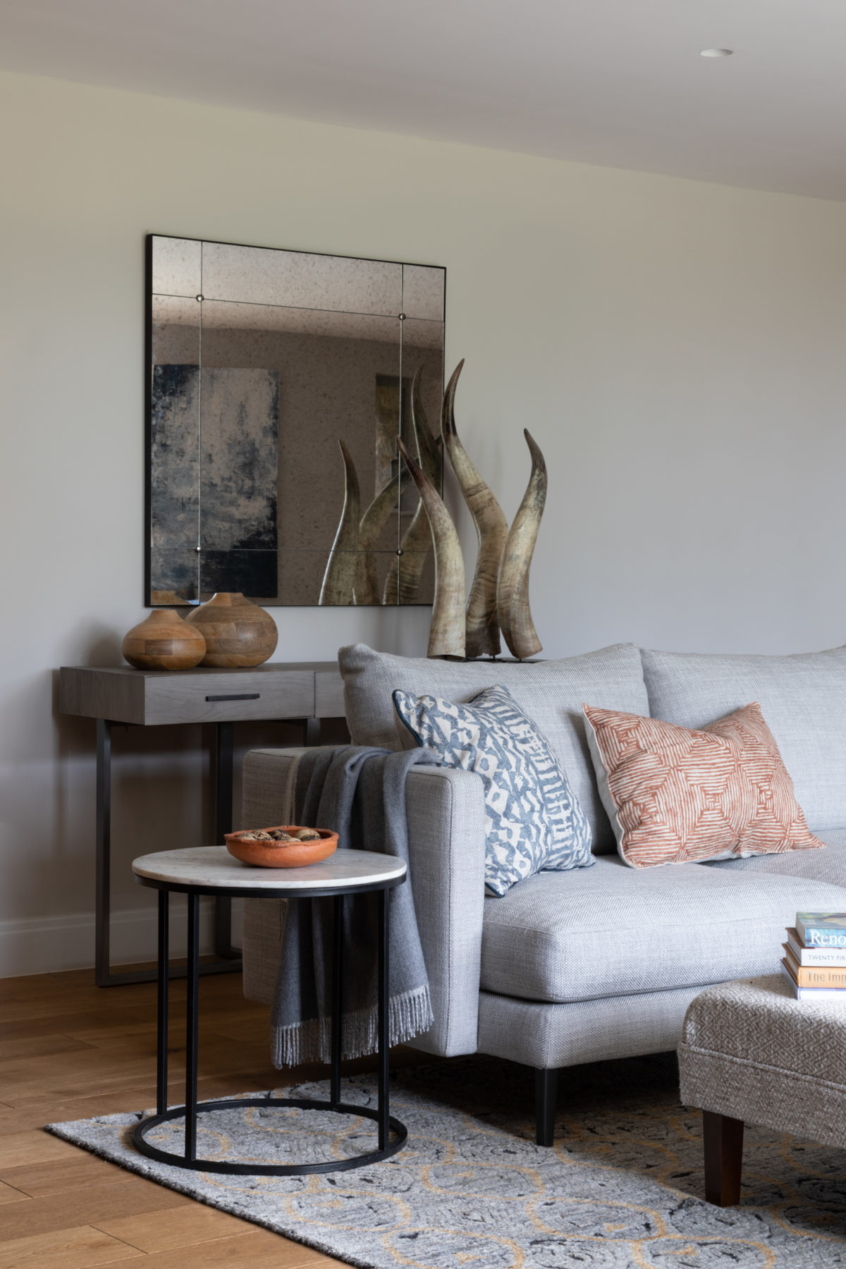 Antique glass mirror in living room. Marble side table. Accessories in groups Blue and orange cushions on corner sofa