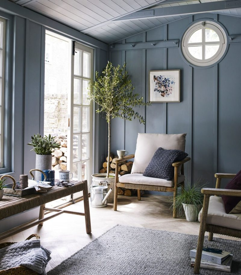 Blue walls for garden room with wood frame chair and French doors to garden