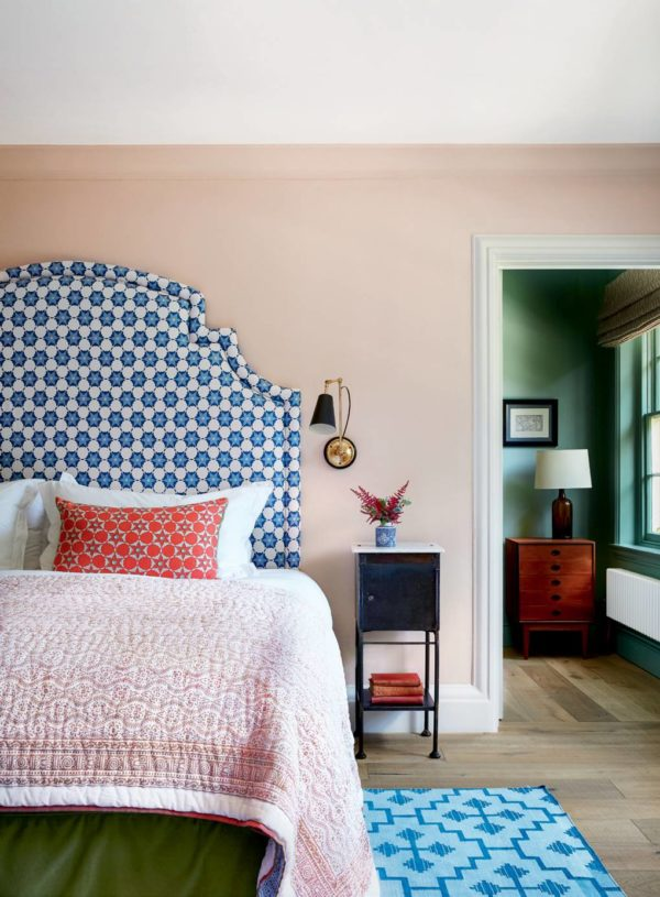 bedroom with blue headboard and soft textures of pink and lilac