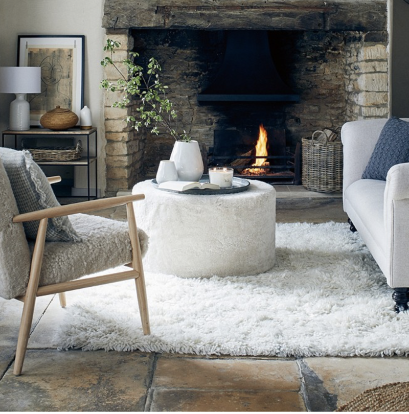 living room with inglenook fireplace and boucle footstool