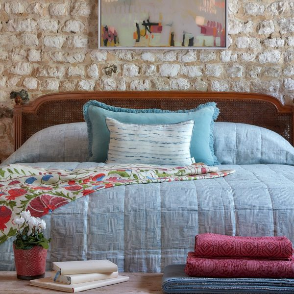 bedroom with stone wall and pretty shades of blue and pink