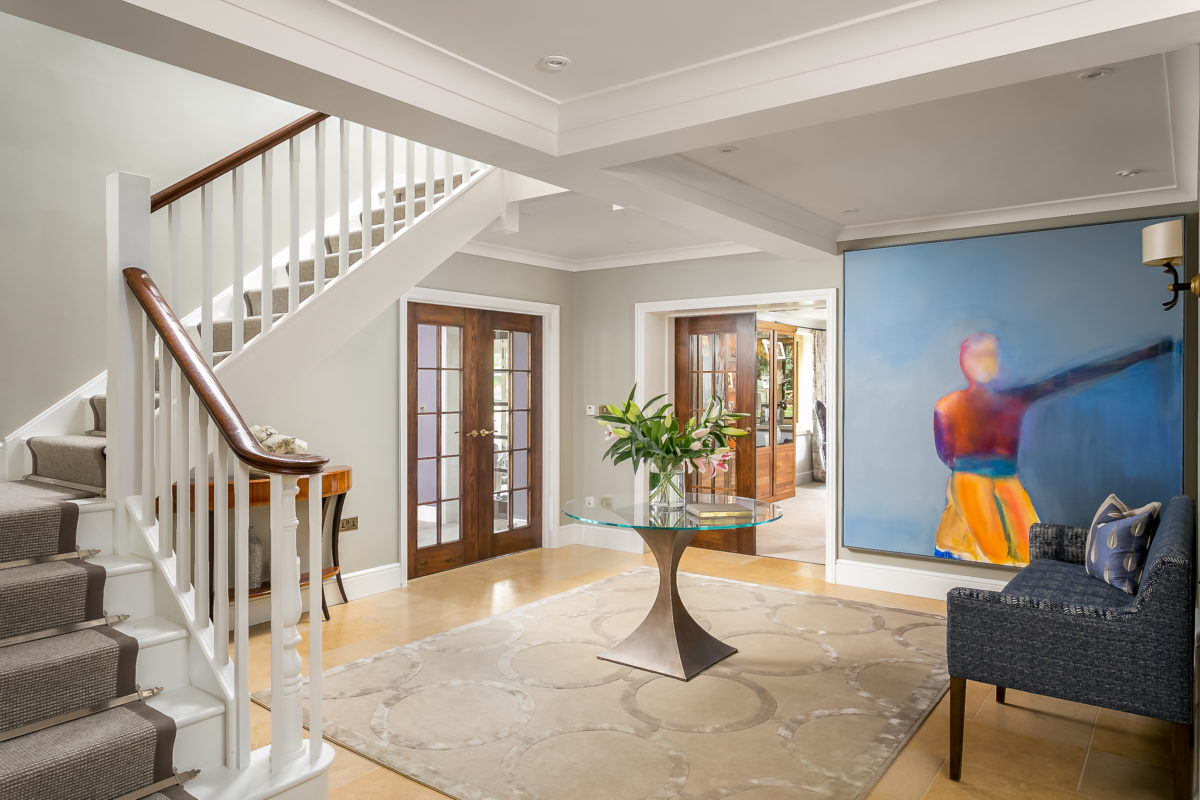 Rug in entrance hall with curved staircase and round pedestal table