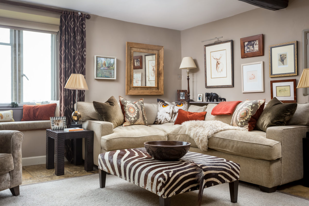 corner sofa with cushions in burnt orange & olive green. Pictures in groups on wall