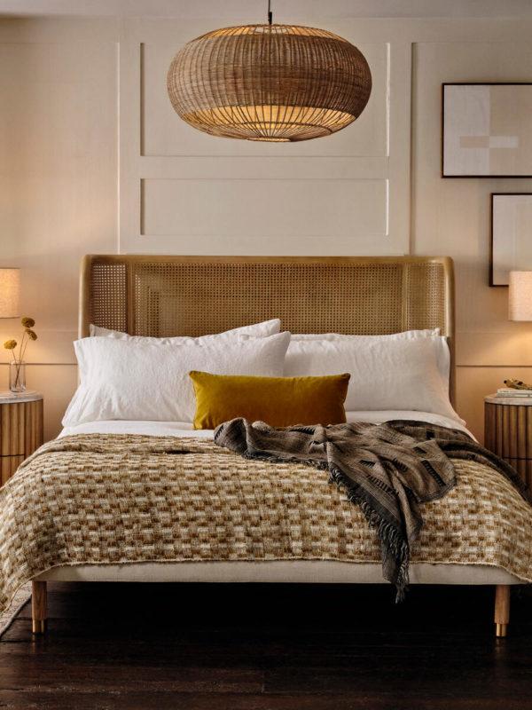 Cane pendant light in bedroom over rattan bed, mustard weave throw & velvet cushions