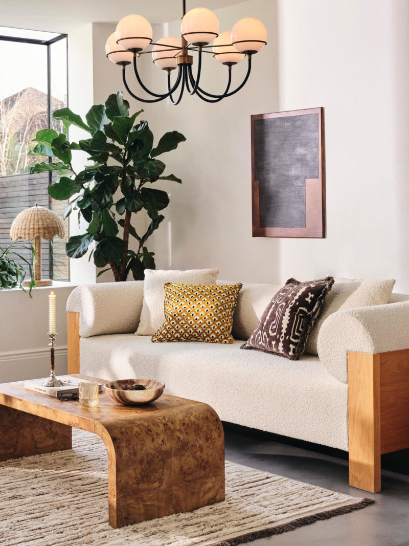 Mid-century sitting room with multi arm chandelier, cream sofa and wood coffee table