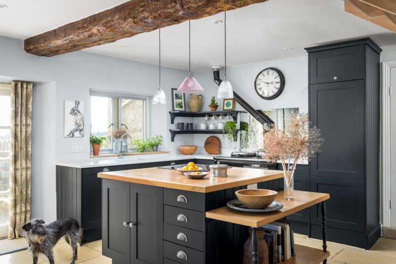 Black kitchen with quartz work surface and oak top on the island unit. Glass pendant lights
