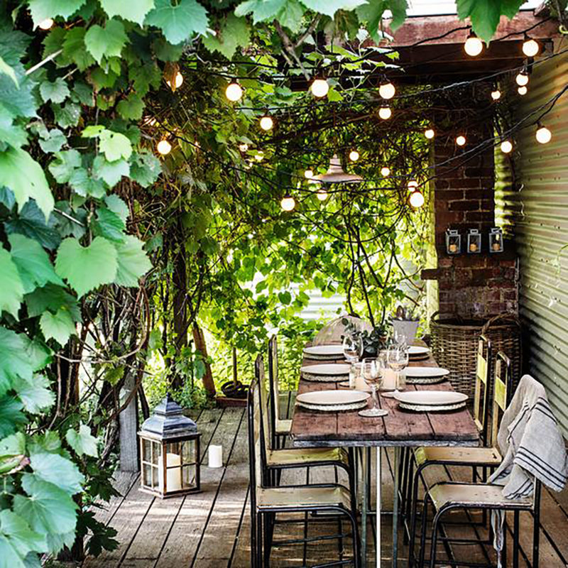 outdoor dining table & chairs with hanging garden lights in loggia